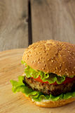 Burger on wooden plate Royalty Free Stock Image