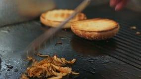 Burgerbrötchen werden auf dem Ofen und den gebratenen Zwiebeln des Chefs Aufruhre auf dem Ofen getrocknet stock footage