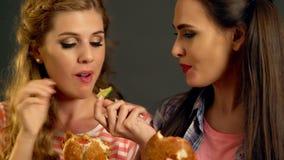 Burgerfrauen, die Schnellimbiß mit Schinken essen stock footage