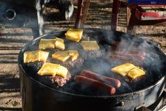 Burgers και σκυλιά που μαγειρεύουν στην καυτή σχάρα Στοκ φωτογραφία με δικαίωμα ελεύθερης χρήσης