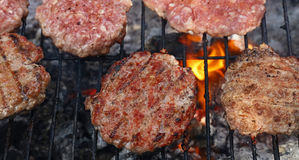 Burgers κρέατος για το χάμπουργκερ που ψήνεται στη σχάρα στη σχάρα φλογών Στοκ Εικόνες