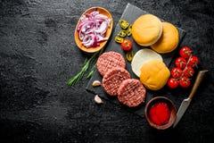 Ακατέργαστα burgers Μαγείρεμα Burger βόειου κρέατος patties στοκ εικόνα με δικαίωμα ελεύθερης χρήσης