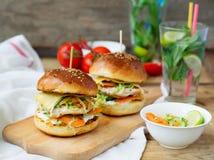 Burgers με το κοτόπουλο και γεμισμένου juicy με το αγγούρι, καρότα α Στοκ εικόνα με δικαίωμα ελεύθερης χρήσης