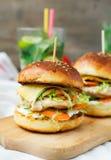 Burgers με το κοτόπουλο και γεμισμένου juicy με το αγγούρι, καρότα α Στοκ φωτογραφία με δικαίωμα ελεύθερης χρήσης