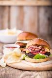Burgers με το μπέϊκον στον ξύλινο πίνακα Στοκ φωτογραφία με δικαίωμα ελεύθερης χρήσης