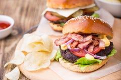 Burgers με το μπέϊκον στον ξύλινο πίνακα Στοκ φωτογραφίες με δικαίωμα ελεύθερης χρήσης