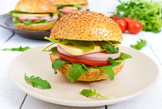 Burgers με το λουκάνικο, το τυρί, την ντομάτα, το arugula και το μαλακό κουλούρι με τους σπόρους σουσαμιού Στοκ εικόνα με δικαίωμα ελεύθερης χρήσης