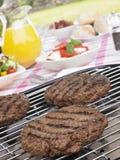 burgers σχαρών που μαγειρεύου&nu Στοκ Φωτογραφίες