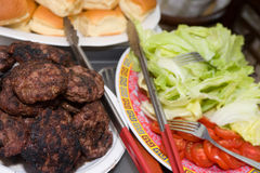 Burgers. Hamburger Patties with toppings and buns nearby Stock Photography
