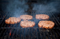 Burgers on barbecue grill. Closeup of beefburgers cooking on barbecue grill Stock Image