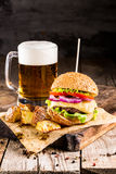 Burgers with beef and fried potatoes and glass of cold beer Stock Photo