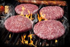 Burgers, Beef and Sausages on a grill with flames stock photography