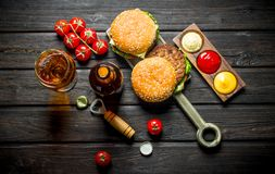 Burgers with beer in a bottle and a glass royalty free stock image