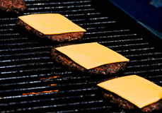 Burgers with cheese on grill Stock Photography