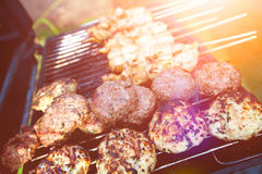 Burgers and chicken kebabs on hot barbecue outdoor in the evening sun. Sizzling burgers and chicken kebabs on hot barbecue outdoor in the evening sun Stock Image