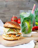 Burgers with chicken and stuffed  juicy with cucumber, carrots a Royalty Free Stock Photo