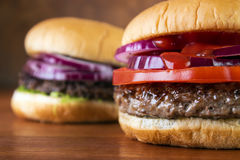 Burgers closeup. On wooden table , shallow DOF Stock Images