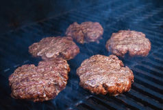Burgers cooking on barbecue. Closeup of beefburgers cooking on barbecue grill Royalty Free Stock Photo