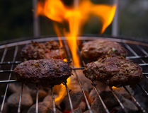 Burgers cooking on barbecue Royalty Free Stock Image