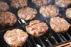 Burgers cooking on the grill Royalty Free Stock Photo