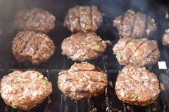 Burgers cooking on the grill Royalty Free Stock Images