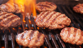 Burgers cooking on grill. Homemaded burgers cooking on garden grill Royalty Free Stock Photography