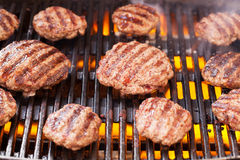 Burgers cooking on grill Stock Image