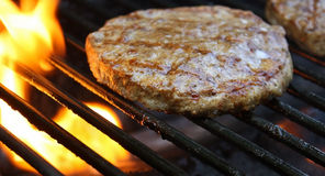 Burgers Cooking Over Flames On The Grill Stock Photos