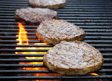 Burgers Cooking Over Flames On The Grill Royalty Free Stock Photo