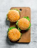 Burgers on the cutting Board. On white wooden background royalty free stock photo