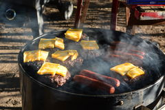 Burgers and dogs cooking on hot grill royalty free stock photo