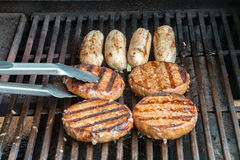 Burgers en worsten die op een gasbarbecue koken Stock Afbeeldingen