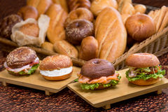 Burgers with fish on wooden plank on bread background Stock Photos