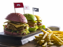 Burgers with french fries isolated. Different color burgers with beef, pork and chicken with french fries on wooden board isolated on white backgound royalty free stock photos