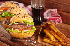 Burgers and fries on a dark wooden background Royalty Free Stock Photography
