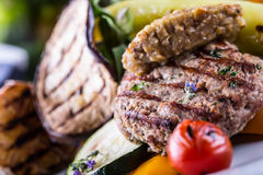 Burgers. Grill burgers. Minced burgers. Roasted burgers with grilled vegetable and herb decoration. Minced meat grilled in a hotel Royalty Free Stock Images
