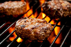 Burgers On The Grill. Close up of three burgers on the grill Royalty Free Stock Photo