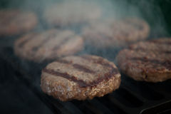 Burgers on a grill Royalty Free Stock Image