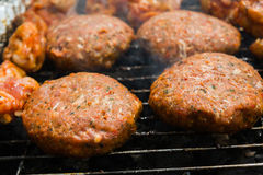 Burgers on a grill. Raw beef burgers on a barbecue grill stock photo