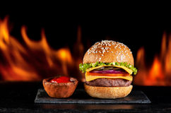 Burgers hamburgers cheeseburgers on fire Royalty Free Stock Photography