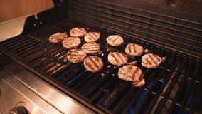 Burgers het Koken bij de Gasgrill stock afbeeldingen