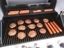 Burgers and hot dogs on the grill Royalty Free Stock Photography