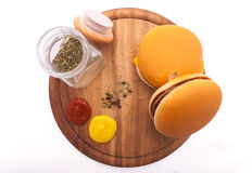 Burgers isolated on the white background and wooden table Stock Photography