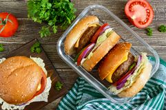 Burgers with juicy cutlet, fresh vegetables, crispy bun with sesame seeds on a wooden table. Traditional fast food. The top view, flat lay royalty free stock photography