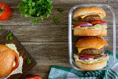 Burgers with juicy cutlet, fresh vegetables, crispy bun with sesame seeds on a wooden table. Traditional fast food. The top view, flat lay stock photography