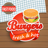 Burgers Label on the wood background. Royalty Free Stock Images