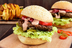Burgers with liver cutlet, tomatoes, pickles, lettuce, spicy sauce and a soft bun with sesame seeds on a cutting board and potato Royalty Free Stock Image