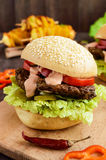 Burgers with liver cutlet, tomatoes, pickles, lettuce, spicy sauce and a soft bun with sesame seeds on a cutting board and potato Royalty Free Stock Photos