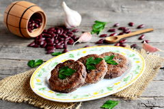 Burgers made from boiled and mashed red beans on a plate. Scattered uncooked red beans, garlic, fresh parsley, small spoon Stock Photos