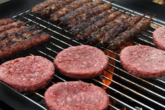 Burgers and meat on skewers on home barbeque. Royalty Free Stock Image